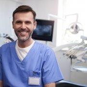 Portrait of smiling dentist in dentist's office